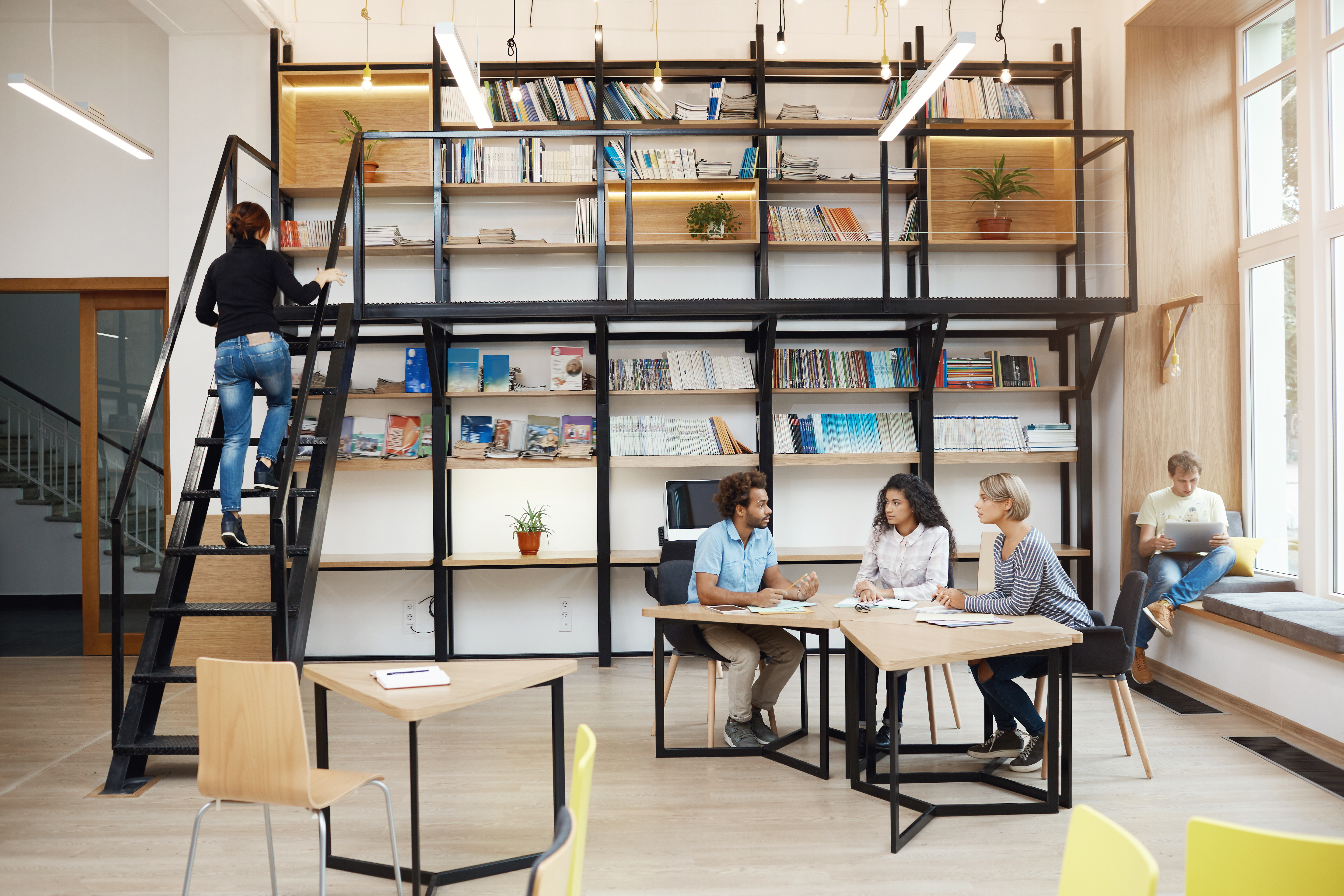 three-young-perspective-startupers-sitting-modern-light-library-meeting-talking-about-new-project-lo